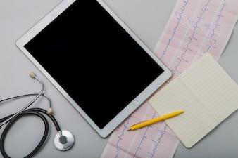 Cardiograma y tableta con bloc de notas
