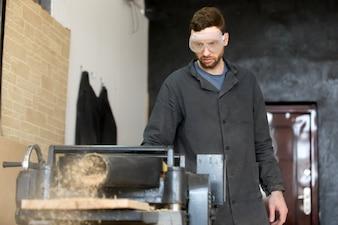 Carpintero en gafas de seguridad trabaja en máquina herramienta