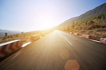 Carretera con punto de fuga al atardecer