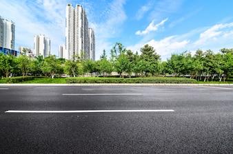 Carretera con un fondo de edificios y parque