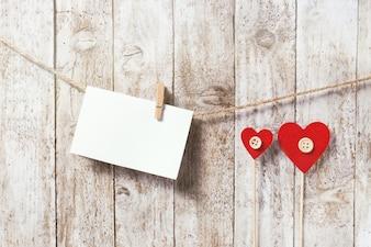 Carta colgando de una cuerda y dos corazones rojos