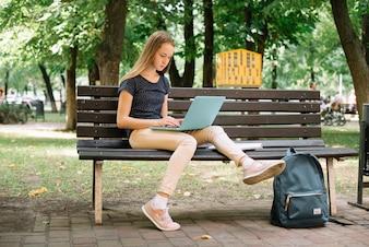 Casual adolescente estudiando con la computadora portátil