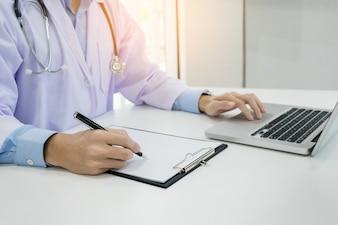 Cerca de médico desconocido masculino sentado en la mesa cerca de la ventana en el hospital y escribiendo en la computadora portátil.