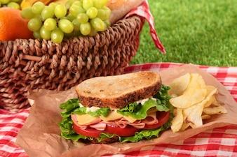 Cesta de picnic y sándwich de jamón y queso