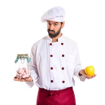 Chef de celebración jarra de vidrio con dulces en una mano y la manzana en otra mano