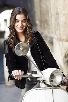 Chica alegre conduciendo una moto blanca