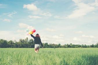 Chica andando con globos de colores