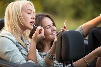 Chica aplicándose brillo de labios en el coche