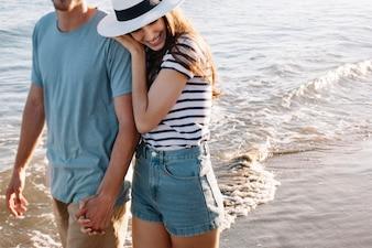 Chica apoyando cabeza en hombro del novio en la playa