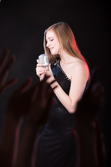 Chica cantando con un vestido negro