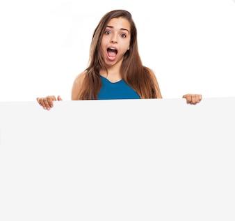 Chica con cara divertida enseñando un letrero