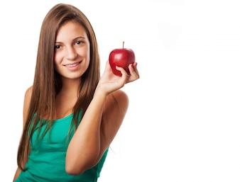 Chica con el pelo largo posando con una manzana