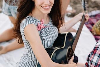 Chica con guitarra por la playa