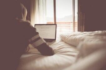 Chica con la computadora portátil en su cama