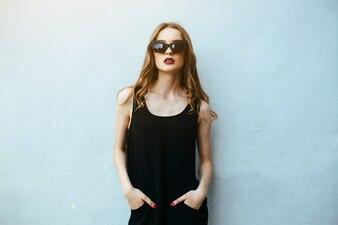 Chica con las manos en los pantalones posando con gafas de sol