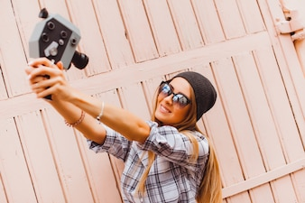 Chica con los brazos estirados apuntándose con una videocamara antigua