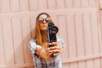 Chica con los brazos estirados con una videocamara antigua