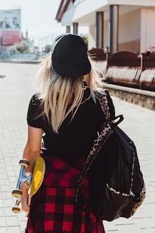Chica con un monopatín en una mano