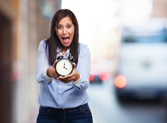 Chica con un reloj despertador