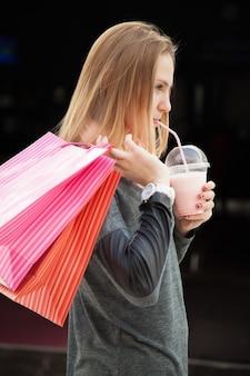 Chica con un vaso y bolsas de la compra