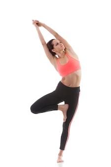 Chica concentrada mostrando un ejercicio de equilibrio