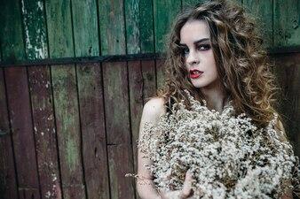 Chica de pelo rizado posando en una pared sucia