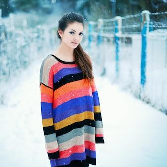 Chica de pie en el campo nevado