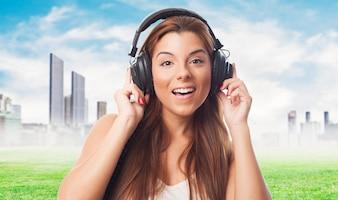 Chica disfrutando de la música contra el paisaje urbano