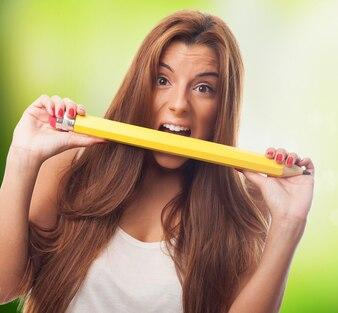 Chica divertida crujido lápiz de color amarillo.