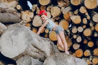 Chica divertida posando con leña de fondo
