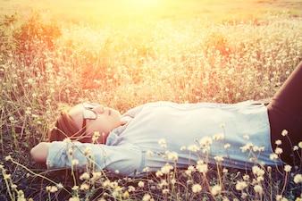 Chica durmiendo en un campo de flores