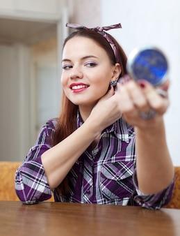 Chica en frente de espejo tratando de pendientes