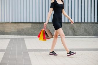 Chica en vestido negro caminando en el pavimento