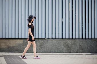 Chica en vestido negro caminando fuera