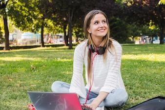 Chica encantadora posando en el parque con la computadora portátil