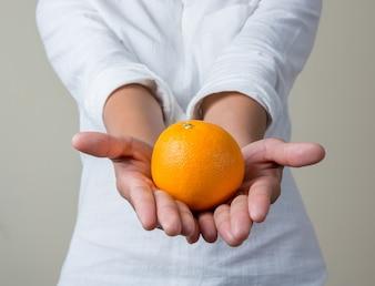 Chica enseñando una naranja