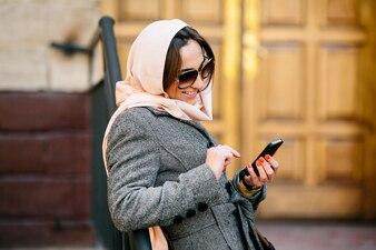 Chica estilosa sonriendo con su móvil