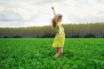 Chica feliz con los brazos arriba en el prado