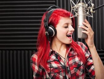 Chica feliz grabando una canción