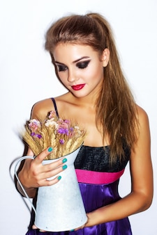 Chica guapa sujetando y mirando un florero