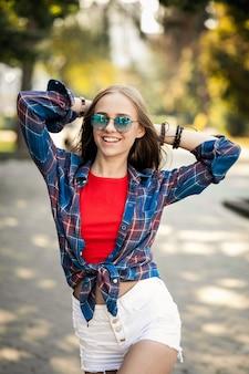 Chica joven con gafas de sol paseando con las manos en la nuca