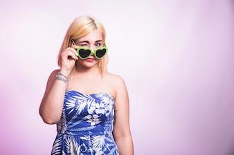 Chica joven guiñando con gafas de sol