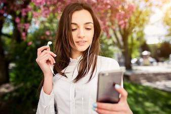 Chica joven poniendose unos auriculares de teléfono