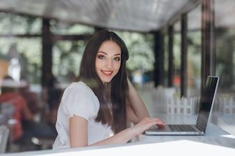 Chica joven sentada en una cafetería con un portátil