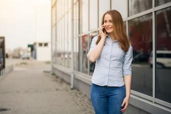 Chica joven sonriendo mientras habla por teléfono