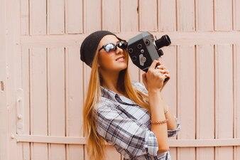 Chica mirando a través de una videocamara antigua
