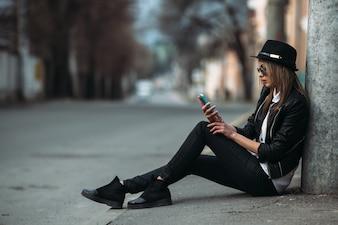 Chica mirando su móvil sentada en el suelo