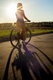 Chica montando en bici al anochecer