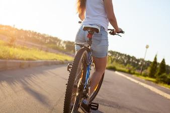 Chica montando en bici con vaqueros