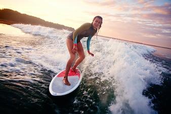 Chica montando una ola